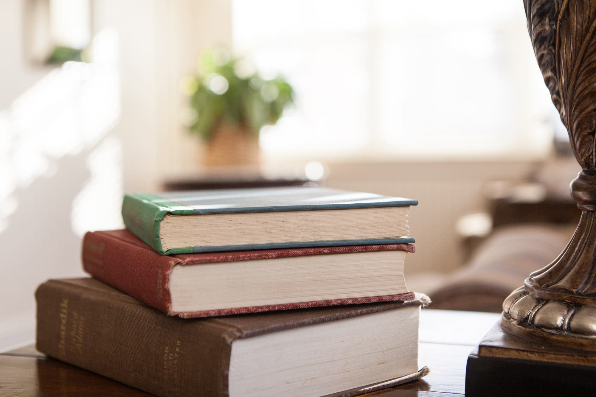 A set of books stacked in the sun room