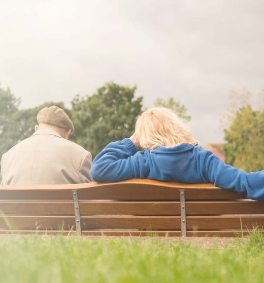 Senior father and adult daughter on a bench having a conversation