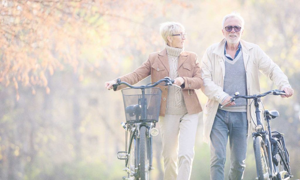 man and woman walking with their bicycles
